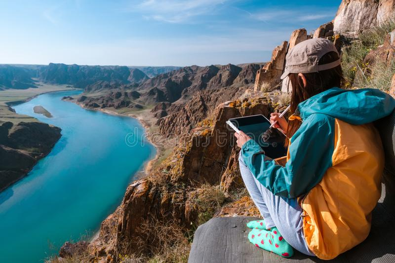 The girl draws the spring landscape of the river on the graphics tablet stock photos