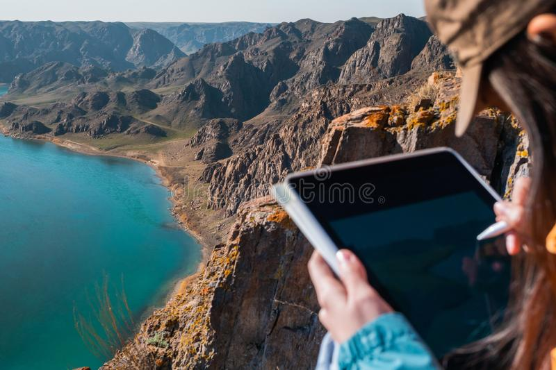 The girl draws the spring landscape of the river on the graphics tablet. Focused on the landscape royalty free stock photos