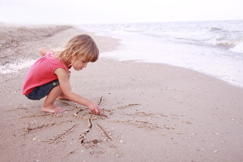 Download Girl Draws A Sun In The Sand On The Beach Royalty Free Stock Photo - Image: 32203115