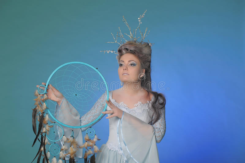 Girl and a dream catcher. On a blue background royalty free stock images