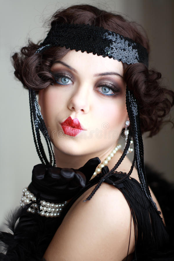 Retro flapper style. Girl dreaming beautiful young flapper woman from roaring 20s looking at camera stock photos