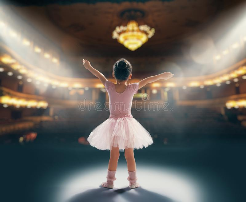 Girl dreaming of becoming a ballerina. Cute little girl dreaming of becoming a ballerina. Child girl in a pink tutu dancing on the stage. Baby girl is studying royalty free stock image