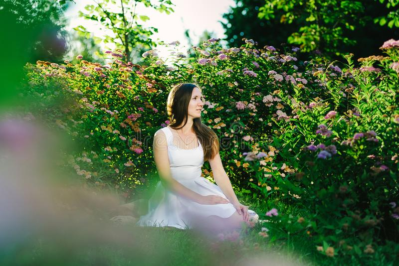 Girl with a dreaming look in a white dress sitting stock image