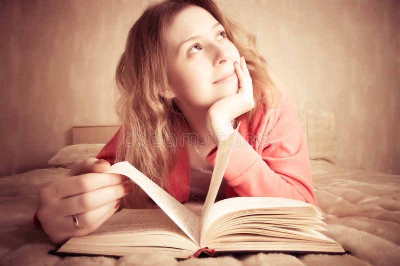 Girl dreams reading the book stock image