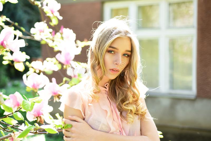 Girl on dreamy face, tender blonde near magnolia flowers, urban background. Lady walks in park on sunny spring day stock photos