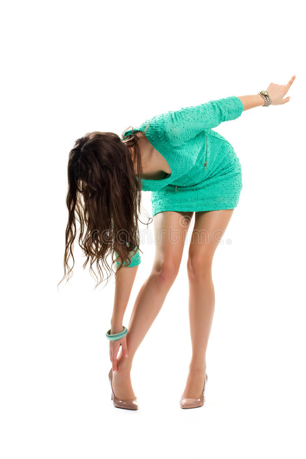 Girl in dress bends down. stock photo