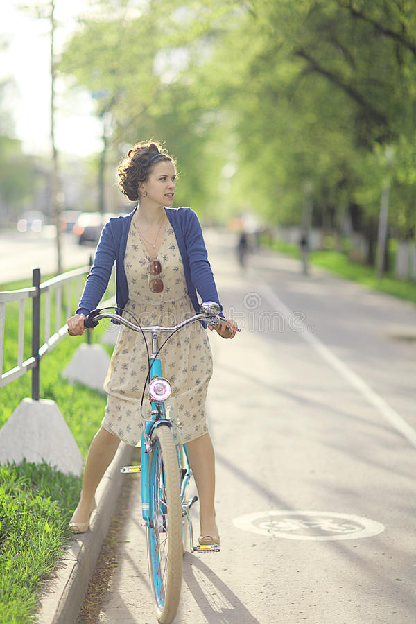Girl in dress on bicycle stock photo