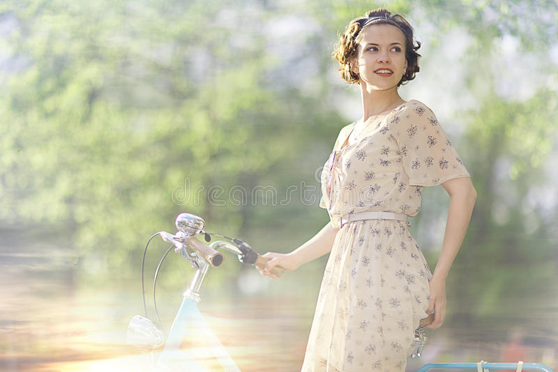 Girl in dress on bicycle stock images