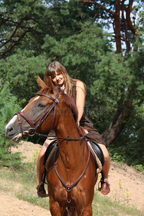 Girl in dress and brown horse portrait in forest stock photos