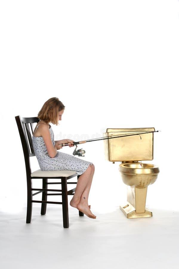 Girl in dress fishing in a golden toilet. Girl fishing in a golden toilet royalty free stock photos