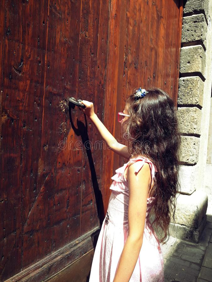 Girl in a dress knocks on an old door. Girl knocks on an old door royalty free stock photography
