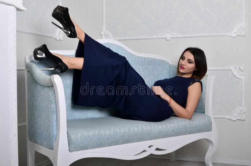 The girl in a dress lies on a blue sofa royalty free stock image