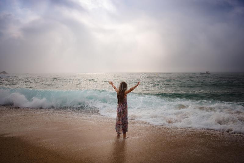 Girl with long hair standing by sea royalty free stock image