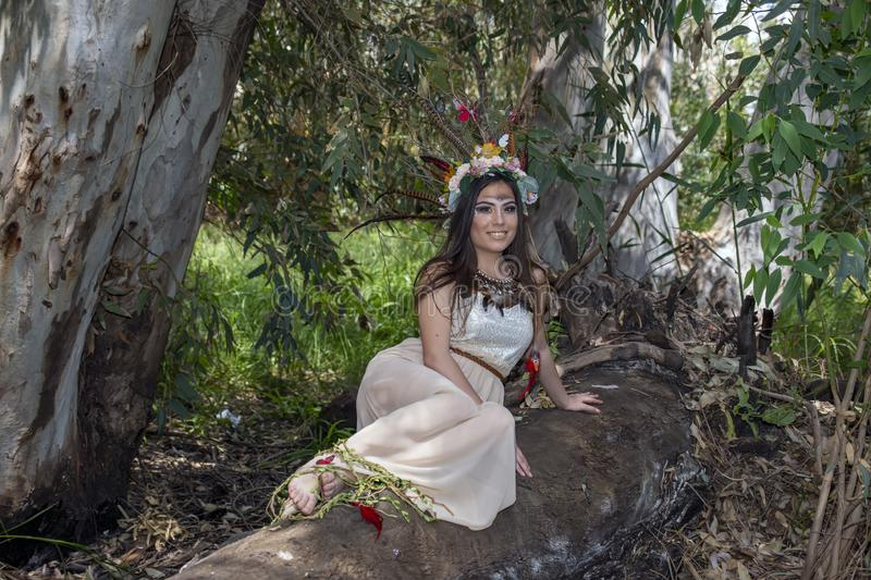 Girl in the dress Pocahontas sitting on a tree trunk on the background of green foliage stock photography