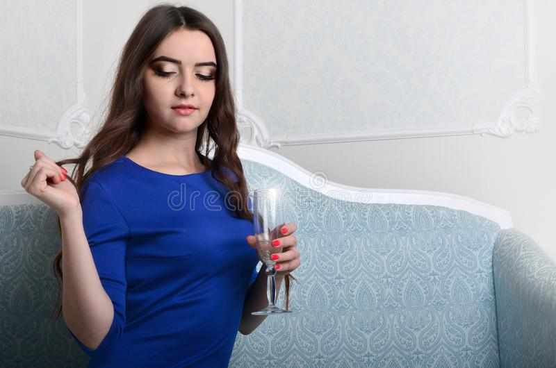 Girl in dress sitting with a glass of champagne royalty free stock photos