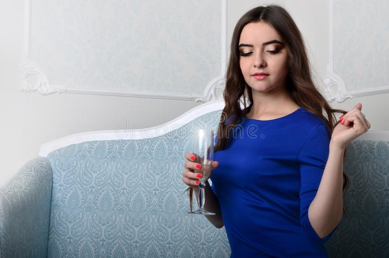 Girl in dress sitting with a glass of champagne royalty free stock images