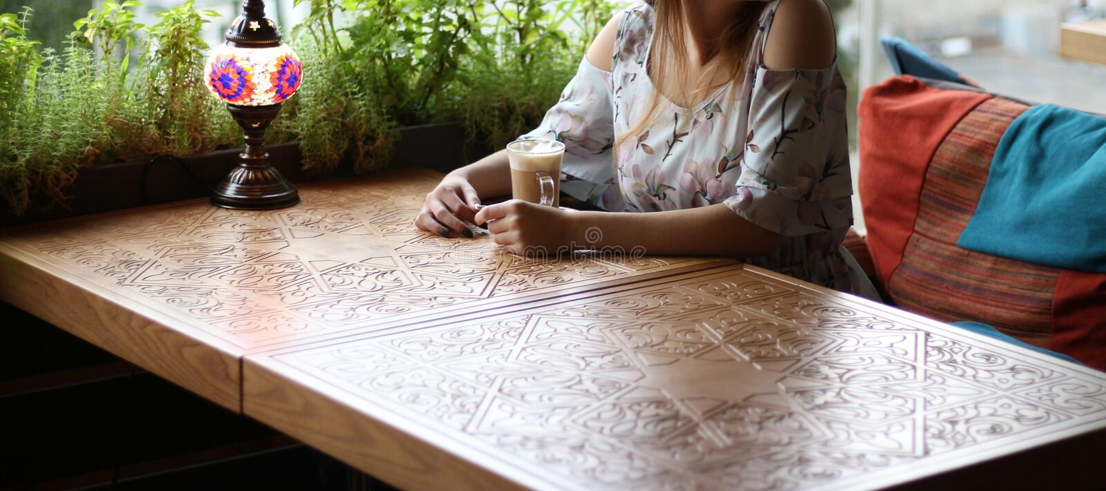 Girl in a dress sitting at a table in a cafe and drinking coffee, waiting for a meeting, a date. Girl in a dress sitting at a table in a cafe and drinking stock photos