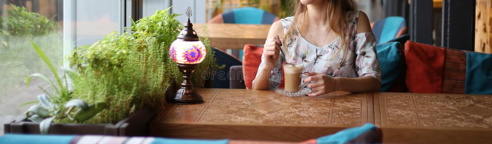 Girl in a dress sitting at a table in a cafe and drinking coffee, waiting for a meeting, a date. Dressed in a white dress with blue and pink flowers, sits by stock images