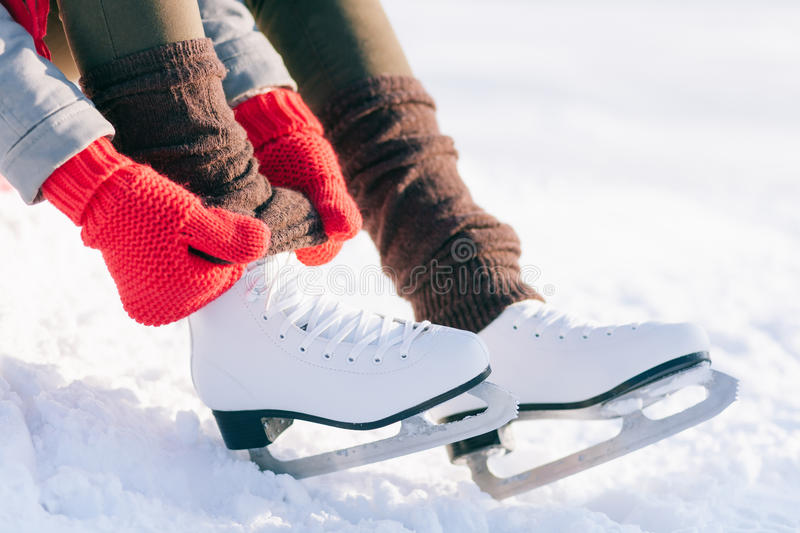 Girl in dress skates mittens tying shoelaces stock photos