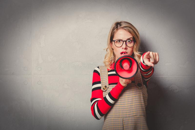 Girl in dress and striped sweater with megaphone stock photo