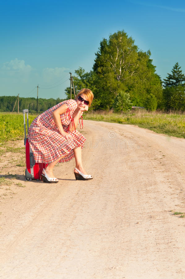 Girl in dress with suitcase. On road royalty free stock images