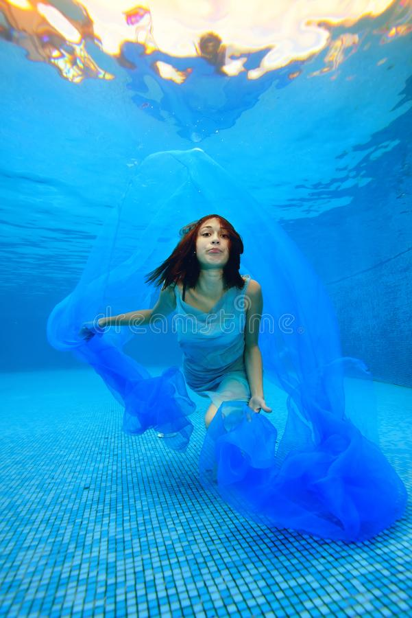 The girl in the dress swims and poses underwater at the bottom of the pool, plays with a blue cloth and looks at the camera agains stock image