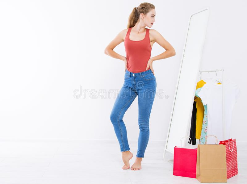 Girl dress up and try on clothes looking in mirror. Shopping and weight loss concept. Copy space. Blank template background. Body. Girl dress up and try on stock photography