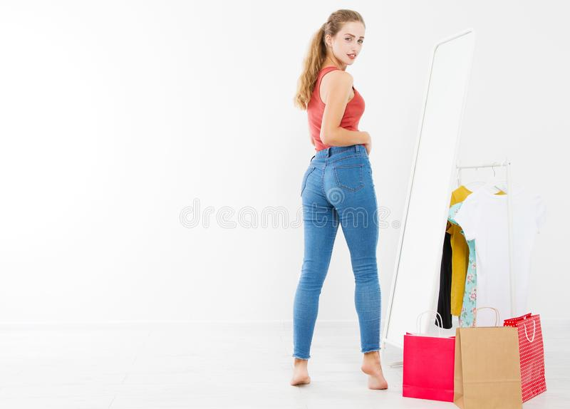 Girl dress up and try on clothes looking in mirror. Shopping and weight loss concept. Copy space. Blank template background. Body. Girl dress up and try on stock image