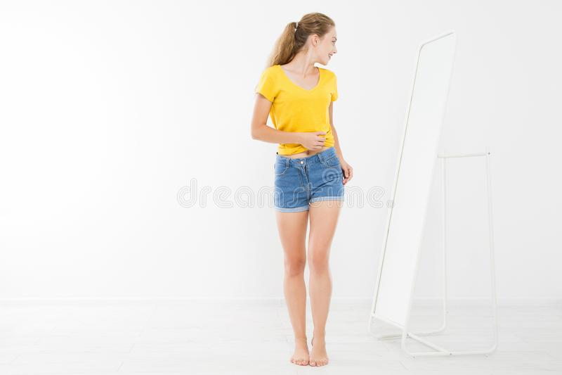 Girl dress up and try on clothes looking in mirror. Shopping and weight loss concept. Copy space. Blank template background. Body. Girl dress up and try on royalty free stock photo