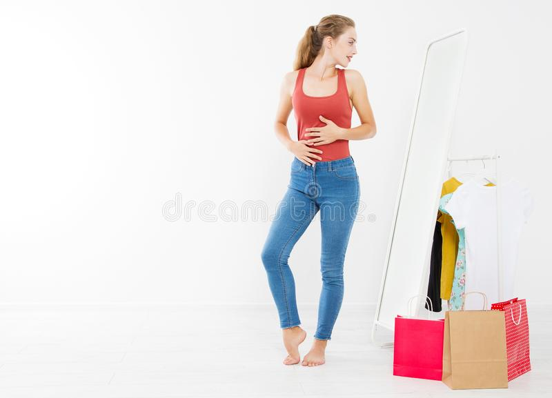 Girl dress up and try on clothes looking in mirror. Shopping and weight loss concept. Copy space. Blank template background. Body. Girl dress up and try on royalty free stock image