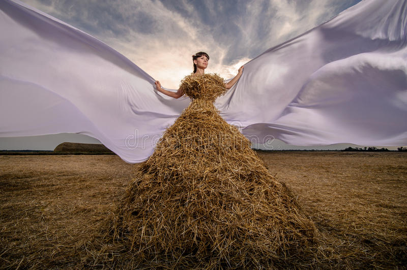 Girl in a dress from wheat , straw fashion royalty free stock images