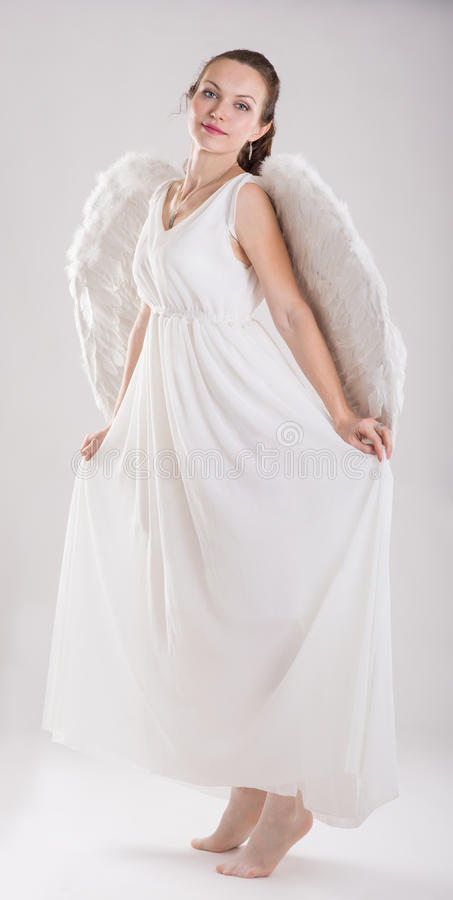 Girl dressed as an angel. A girl dressed as an angel on a light background stock image