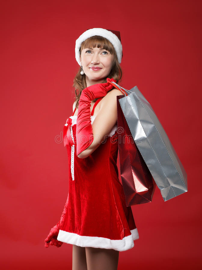 Girl dressed as Santa with a bag of shopping stock photos