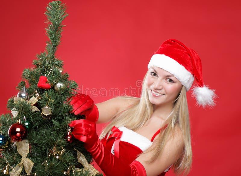 Girl dressed as Santa and a christmas fur-tree stock photo