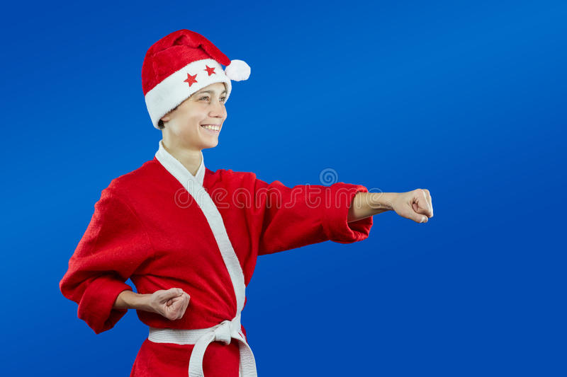 Girl in dressed as Santa Claus beats punch hand. Girl in dressed as Santa Claus beats punch royalty free stock image