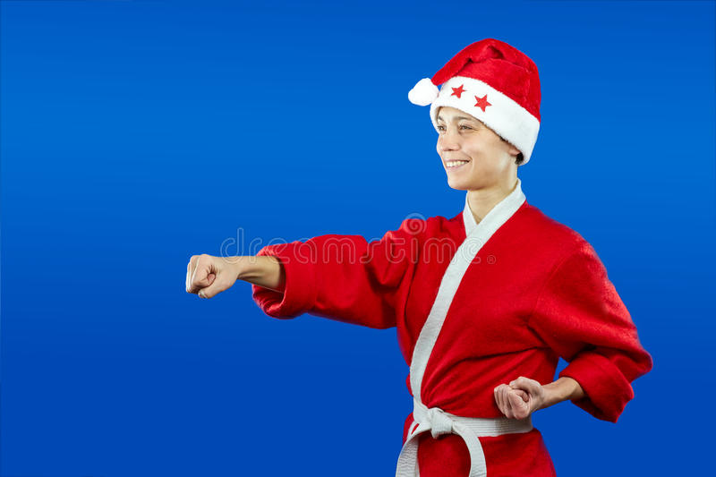 Girl in dressed as Santa Claus beats punch hand. Girl in dressed as Santa Claus beats punch royalty free stock photography