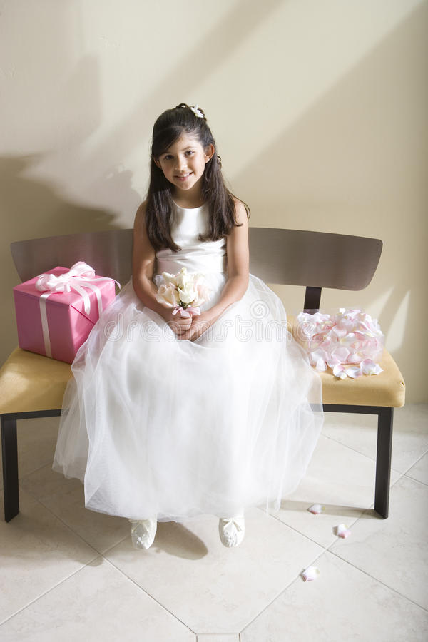 Girl (8-10), dressed in bridesmaid dress, sitting beside wedding gift on bench, smiling, front view, portrait stock image