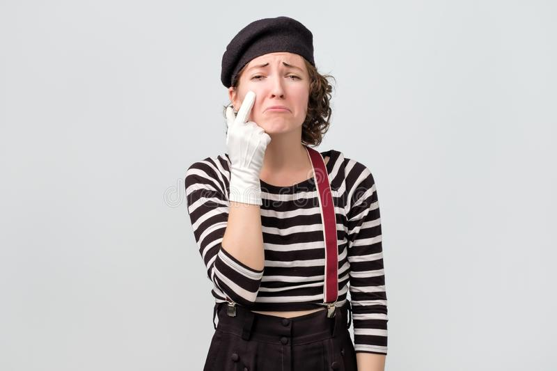 Girl dressed like mime wiping tears from eyes with fingers royalty free stock images
