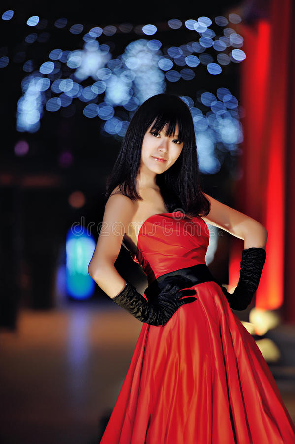 A girl dressed in a red evening dress. In the darkness, in the context of classical Chinese palace royalty free stock photography