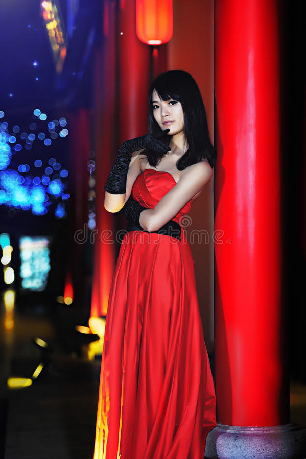 A girl dressed in a red evening dress. In the darkness, in the context of classical Chinese palace stock image