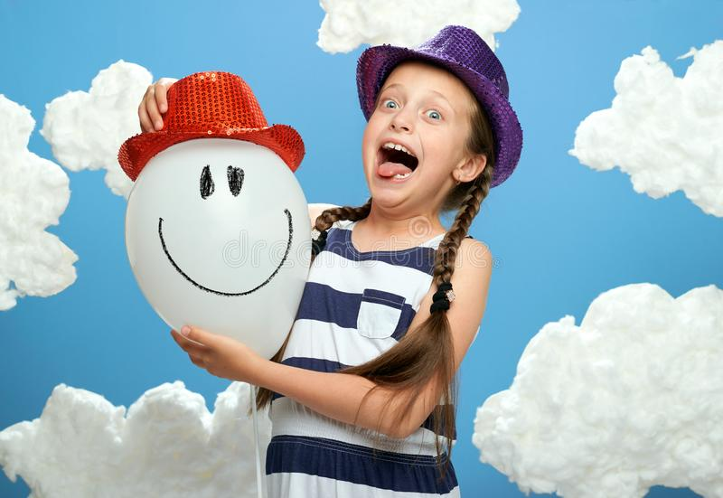 Girl dressed in striped dress and color hat posing on a blue background with cotton clouds, white air balloon, the concept of summ stock photography