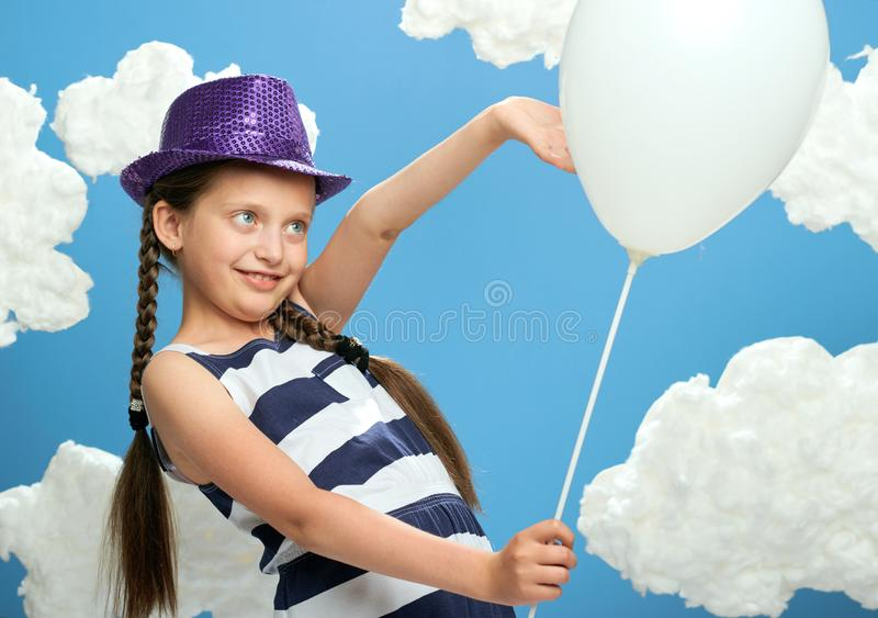 Girl has a big dandelion in her hands, dressed in striped dress, posing on a blue background with cotton clouds, the concept of su. Mmer, holiday and happiness stock images