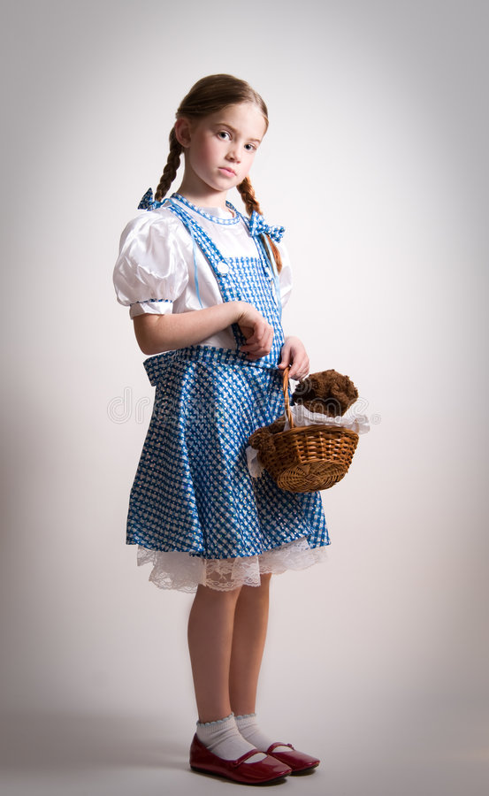 Girl dressed up as Dorothy from Oz. A girl is dressed up as Dorothy from Oz - with a little attitude royalty free stock photography