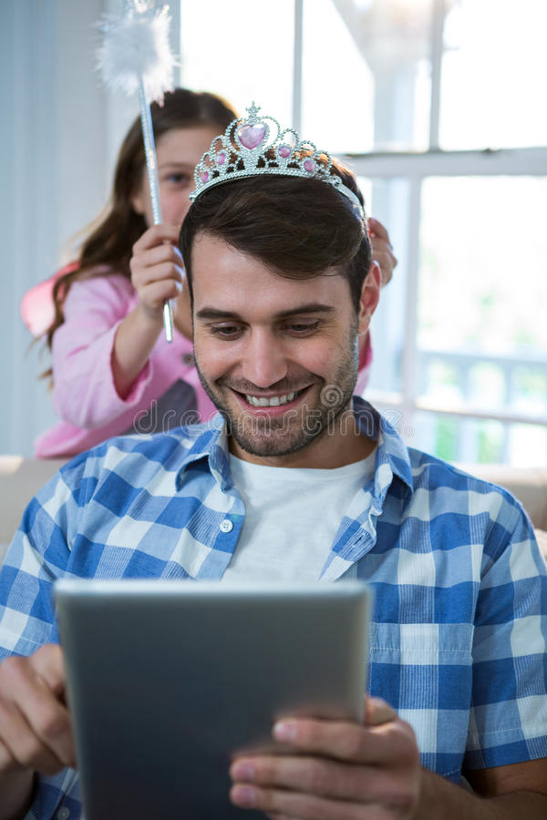 Girl dressed up in a fairy costume placing tiara on fathers head royalty free stock photo