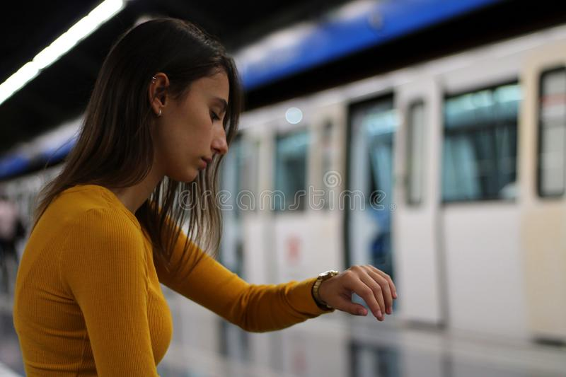 Girl dressed in yellow waiting for the subway car on the underground and watching the time royalty free stock images