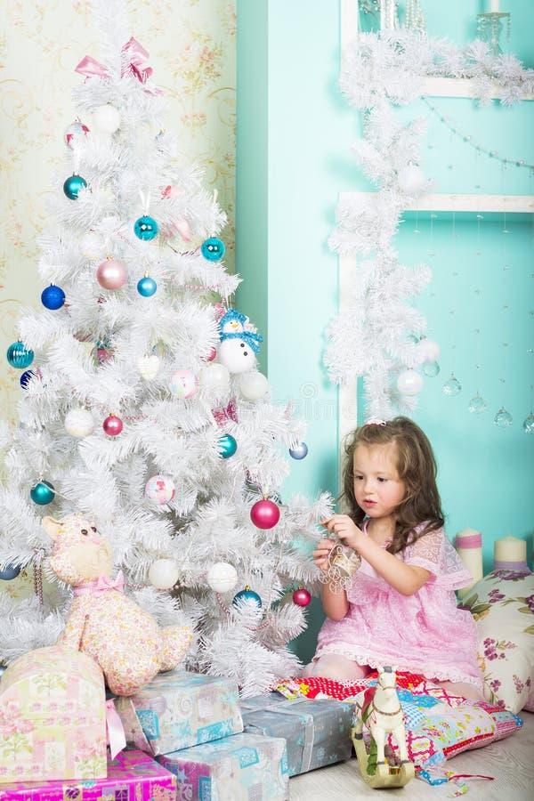 Girl dresses up Christmas tree stock photo