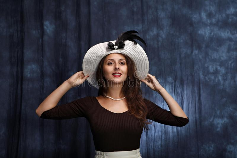 Girl dressing old fashined hat. Young brunette girl dressing old fashined hat with the fields royalty free stock photography
