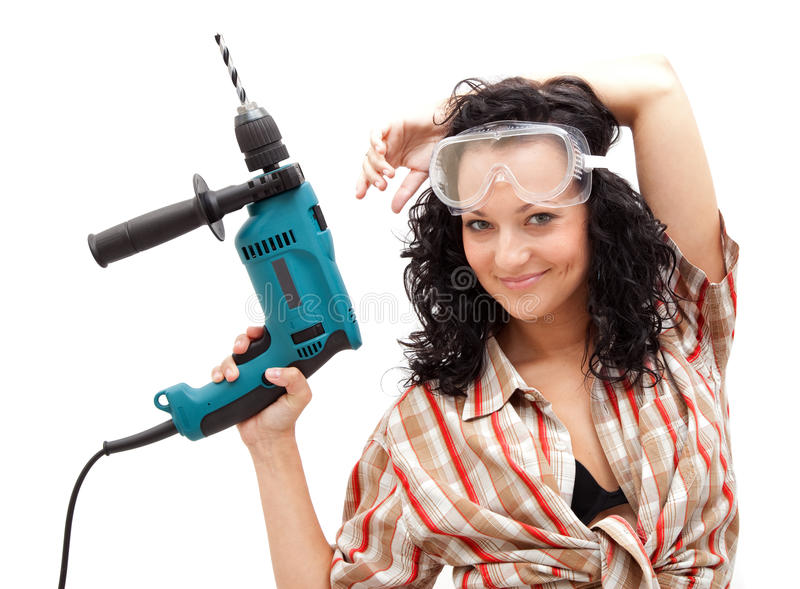 Girl with drilling machine. A young smiling female worker with a drilling machine in her hand royalty free stock image