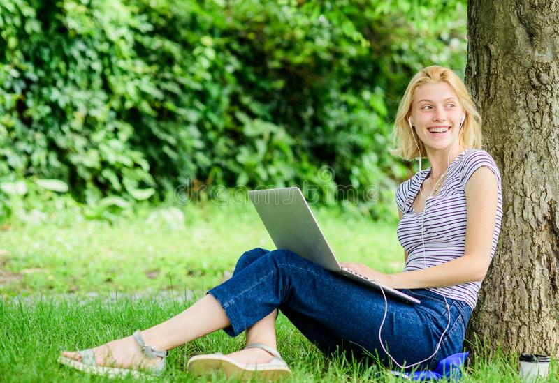 Girl drink coffee to go. Relax in park. modern woman with computer outdoor. summer online. Morning chart. Pretty woman royalty free stock photography