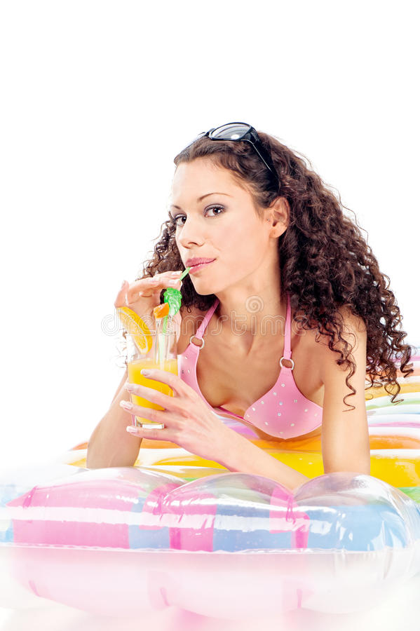 Girl drink juice on air mattress stock photography